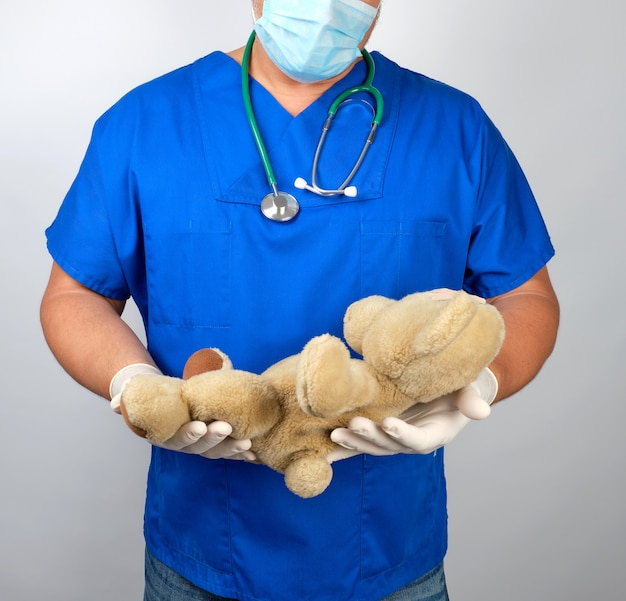 Medico in uniforme blu e guanti in lattice bianco in possesso di un orsacchiotto marrone