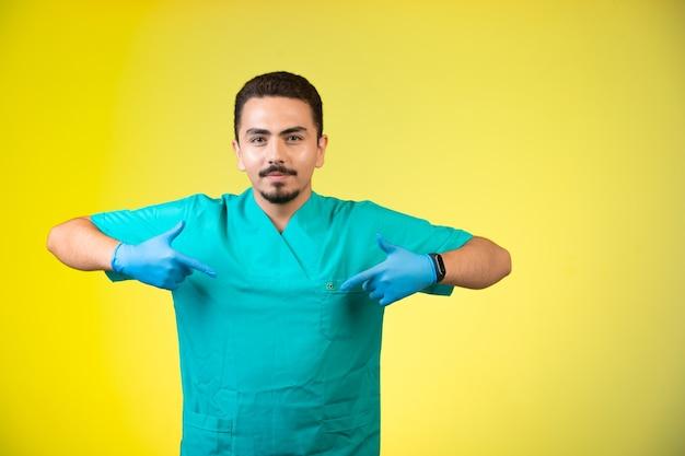 Medico in uniforme e maschera a mano che indica se stesso.