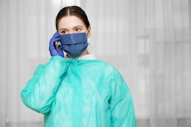 Medico in uniforme protettiva tiene in mano il telefono, la donna chiama un'ambulanza sul telefono, i social network