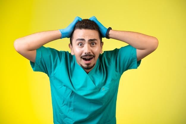 Medico in uniforme verde e maschera a mano che abbraccia la sua testa perché è stanco.