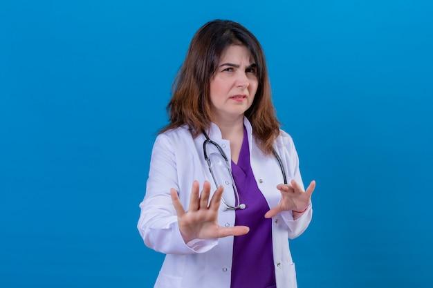 Medico invecchiato centrale che indossa le camice bianche e con lo stetoscopio che alza le palme nel gesto di rifiuto e di arresto, espressione disgustata sopra la parete blu isolata