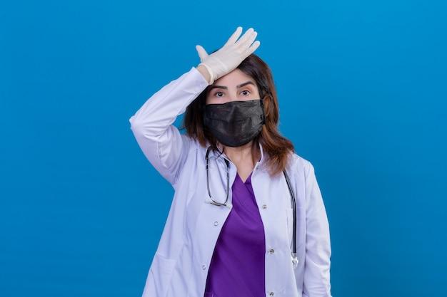 Medico invecchiato centrale indossando camice bianco in maschera protettiva nera e con lo stetoscopio con la mano sulla testa per errore