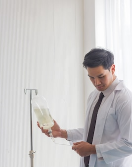 Medico maschio asiatico che esamina una bottiglia di soluzione salina per verificare la disponibilità del dispositivo