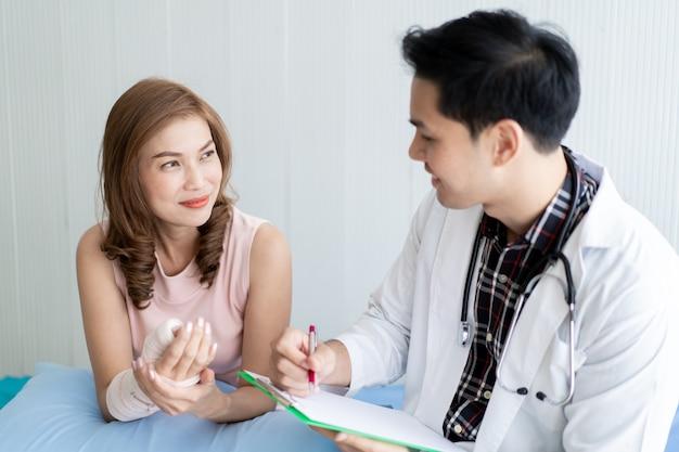 Medico maschio asiatico spiega e mostra il risultato dell'esame al suo paziente in ospedale