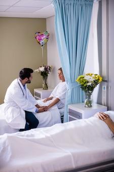 Medico maschio che consola paziente senior femminile