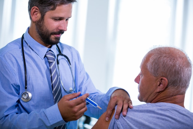 Medico maschio che dà un'iniezione ad un paziente