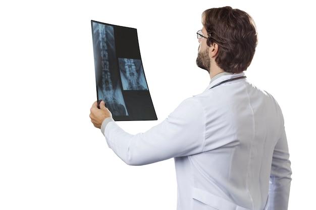 Medico maschio che esamina una radiografia su una parete bianca.
