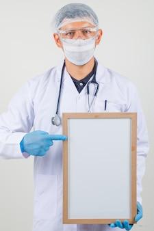 Medico maschio che indica dito al bordo bianco in vestiti protettivi