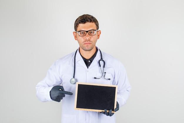 Medico maschio che indica dito alla lavagna in abito bianco medico