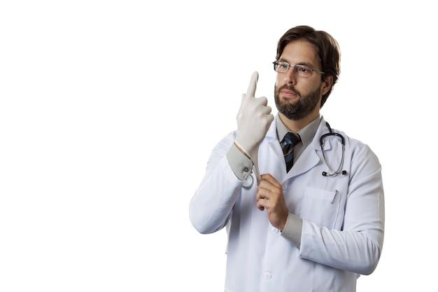 Medico maschio che indossa i guanti di lattice su una parete bianca.