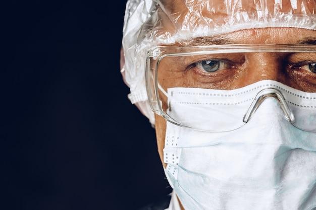 Medico maschio che indossa maschera protettiva e occhiali. sfondo scuro