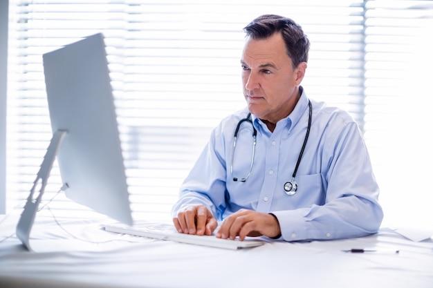 Medico maschio che lavora al personal computer