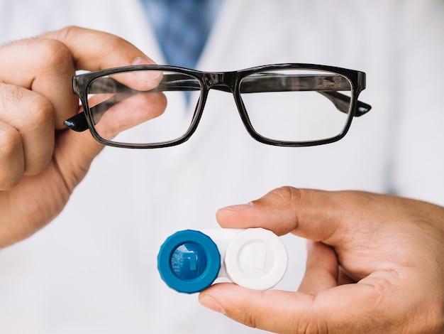 Medico maschio che mostra gli occhiali neri e le lenti a contatto