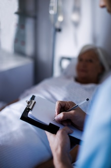Medico maschio che scrive una prescrizione su una lavagna per appunti