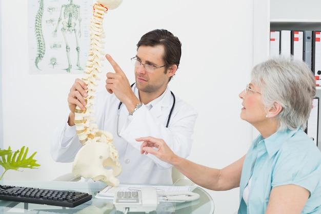 Medico maschio che spiega la spina dorsale ad un paziente senior