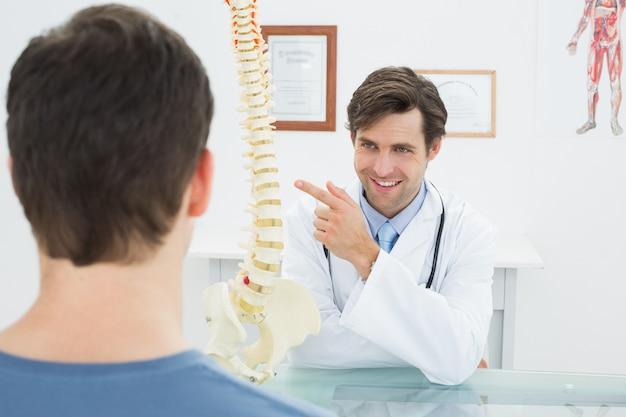 Medico maschio che spiega la spina dorsale ad un paziente