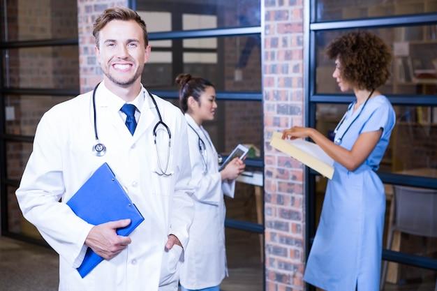 Medico maschio che sta biblioteca vicina con la lavagna per appunti e colleghi che stanno dietro e che discutono