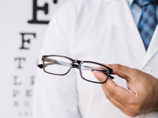Medico maschio che tiene un paio di occhiali in mano