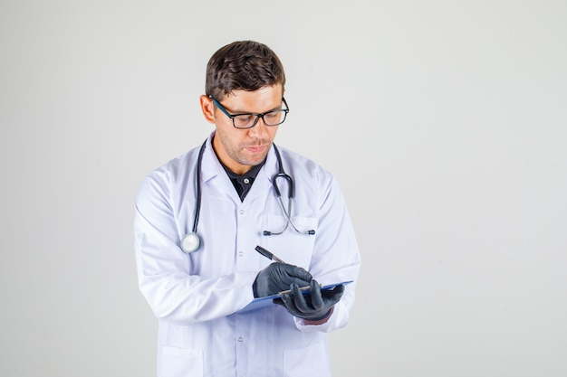 Medico maschio nella prescrizione medica bianca di scrittura dell'abito