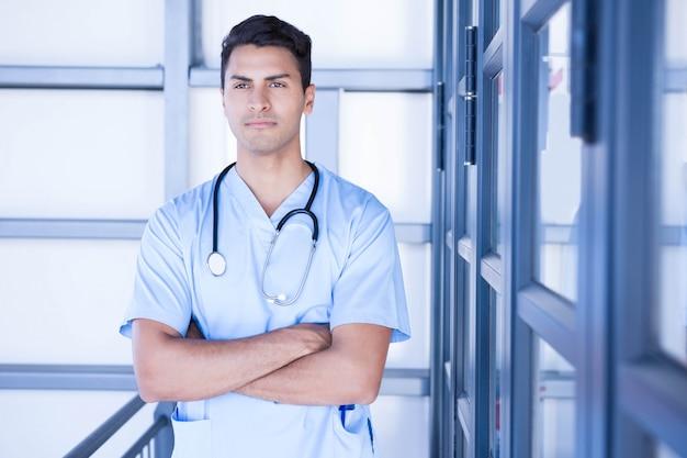 Medico maschio serio che sta con le armi attraversate in ospedale
