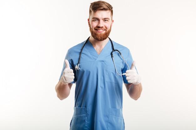 Medico maschio sorridente che mostra i pollici aumenta il gesto con due mani