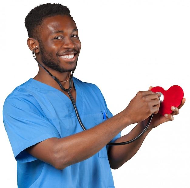 Medico maschio sorridente felice con il cuore della tenuta dello stetoscopio