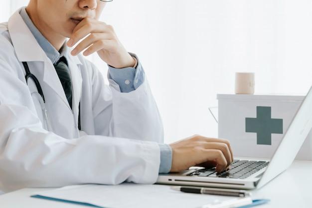 Medico maschio usa computer, ricerca e analisi, analisi delle malattie e registra informazioni sui pazienti,