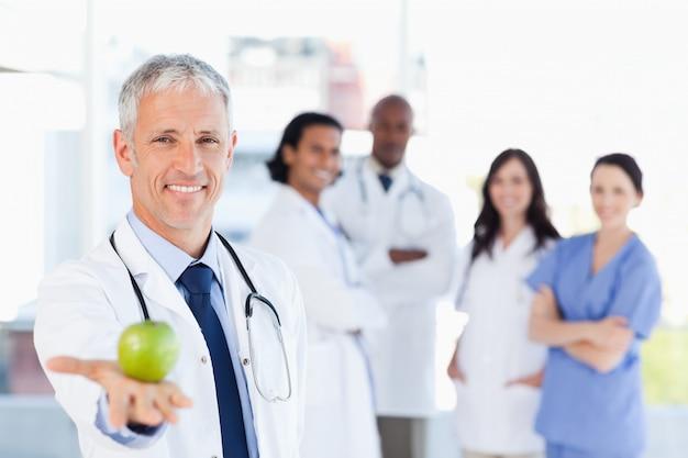 Medico maturo che tiene una mela mentre il suo gruppo di medici sta esaminandolo