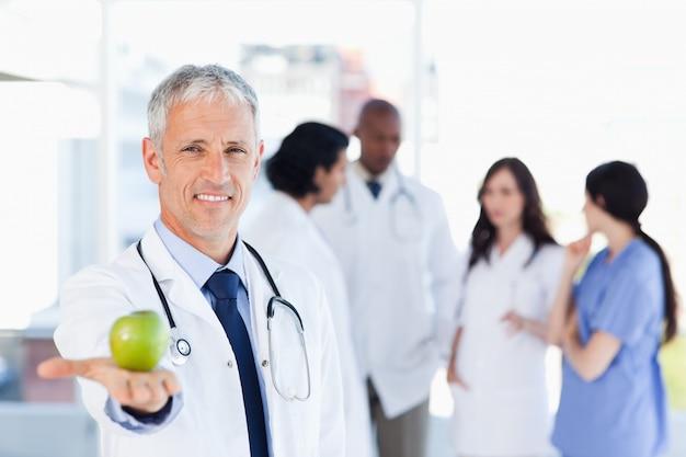 Medico maturo che tiene una mela nella sua mano destra