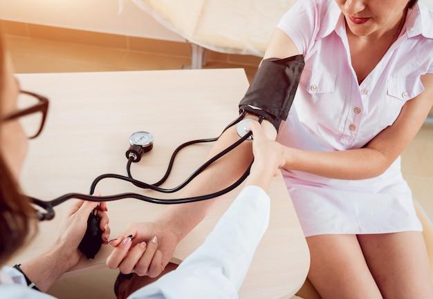 Medico misura la pressione di una donna.