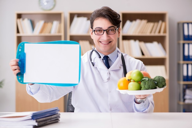 Medico nel concetto stante a dieta con la frutta e le verdure