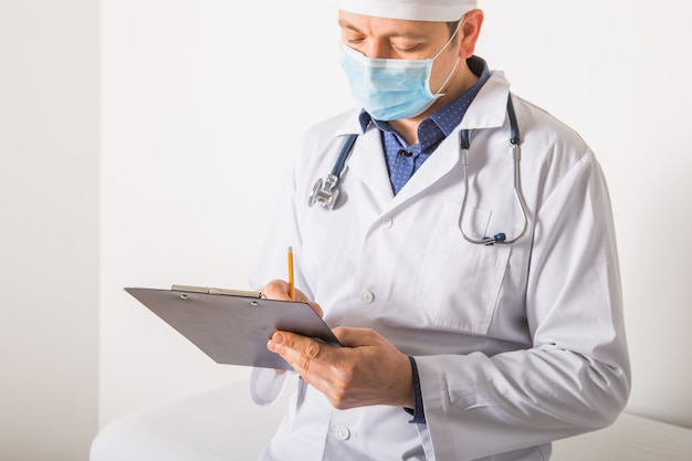 Medico nella maschera con lo stetoscopio che scrive prescrizione di rx sulla lavagna per appunti su fondo bianco, primo piano. servizio medico