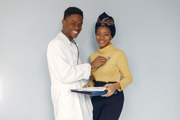 Medico nero in uniforme bianca con uno stetoscopio