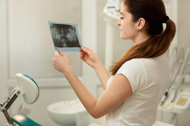 Medico o dentista femminile che esamina raggi x. concetto di assistenza sanitaria, medica e radiologia