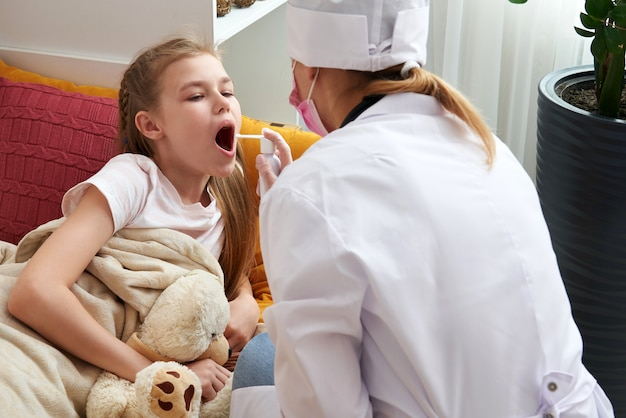 Medico pediatra utilizzando spray medico per la ragazza a casa, mal di gola