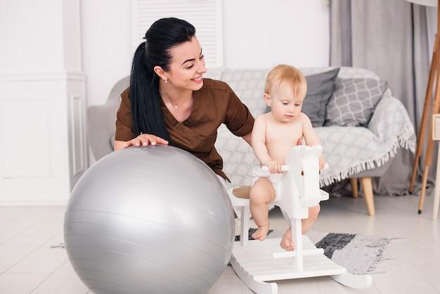 Medico per bambini gentile e amichevole che gioca con la bambina. piccolo bambino sorridente che gioca su un cavallo giocattolo di legno nella stanza accogliente.
