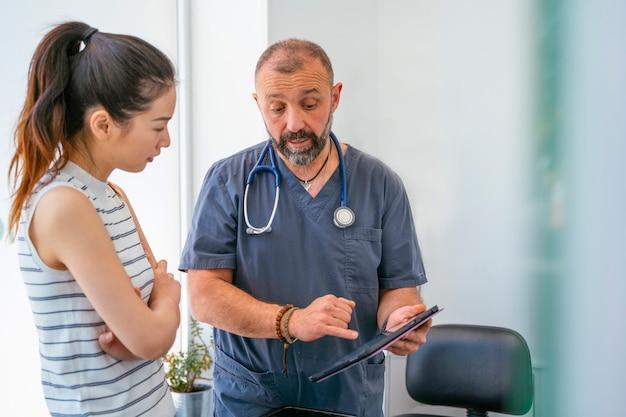 Medico professionista che spiega il sintomo malato di un animale domestico malato ad una donna preoccupata.
