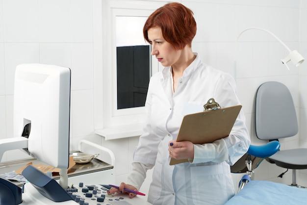 Medico professionista con la lavagna per appunti vicino alla macchina moderna di ultrasuono in clinica