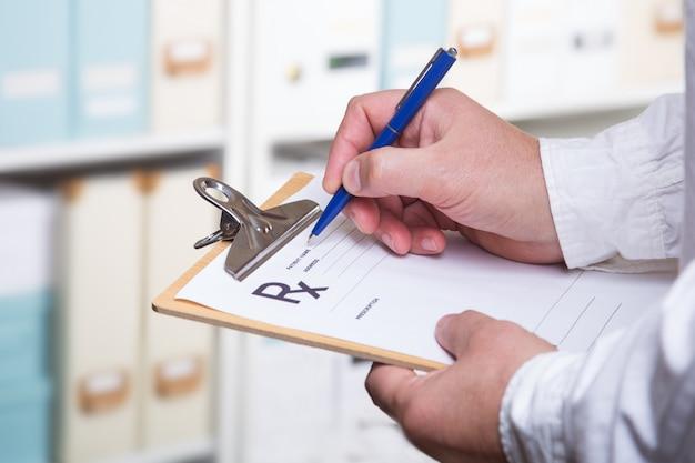 Medico riempiendo l'elenco dei reclami dei pazienti ritagliato sul cuscinetto fisico, esame, prevenzione delle malattie, reparto, prescrizione di rimedi, concetto di stile di vita sano.