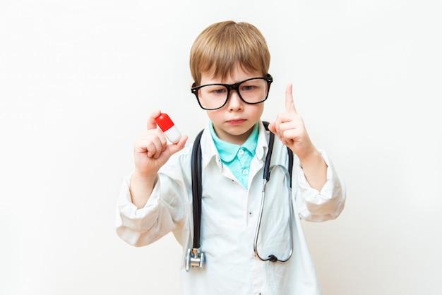 Medico rigoroso del ragazzo del bambino su bianco