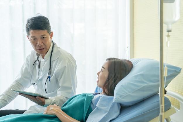 Medico senior asiatico che si siede sul letto di ospedale e che discute con il paziente femminile
