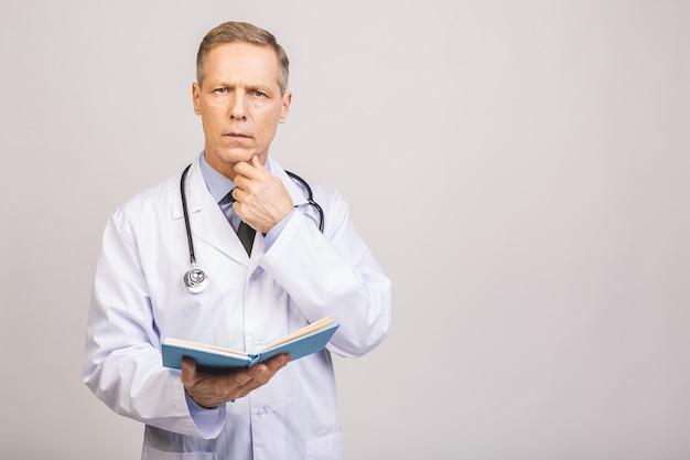 Medico senior che legge un libro isolato sopra la parete grigia.