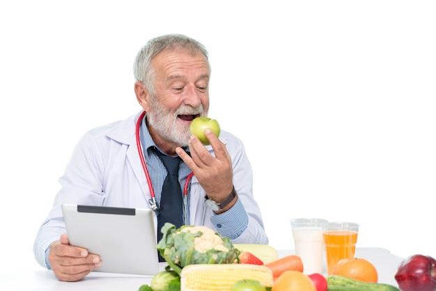 Medico senior in nutrizionista con frutta sana, cibi e bevande sul tavolo