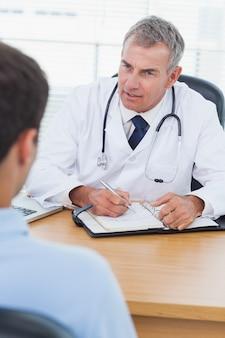 Medico serio che prescrive la droga al suo paziente