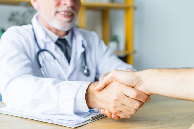 Medico sorridente che agita mano del paziente