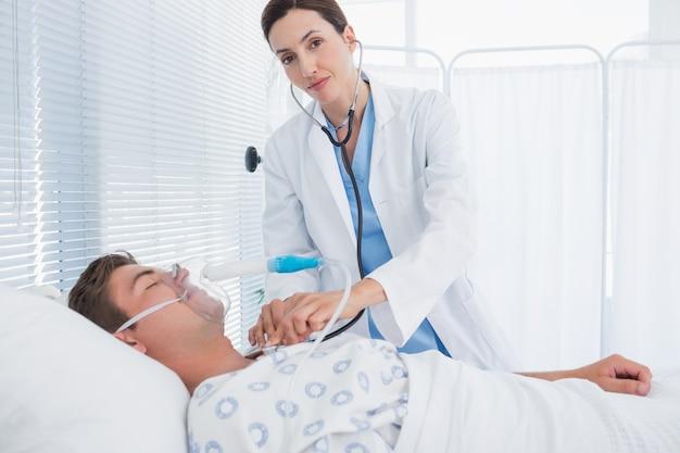 Medico sorridente che auscultating il suo petto dei pazienti