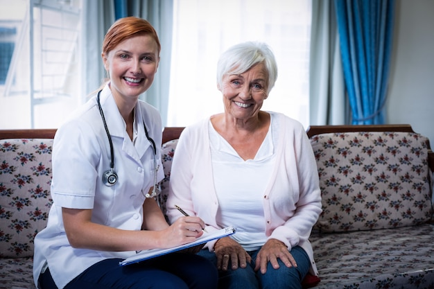 Medico sorridente che consulta la donna senior