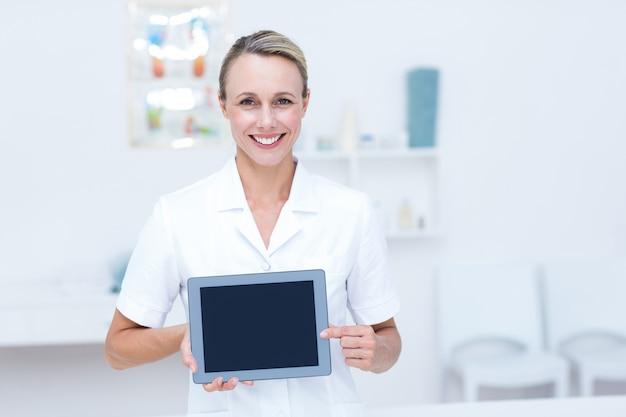 Medico sorridente che esamina macchina fotografica e che mostra compressa