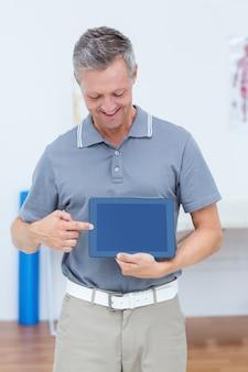 Medico sorridente che mostra compressa digitale