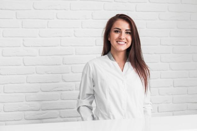 Medico sorridente che si siede davanti alla parete di mattoni bianca